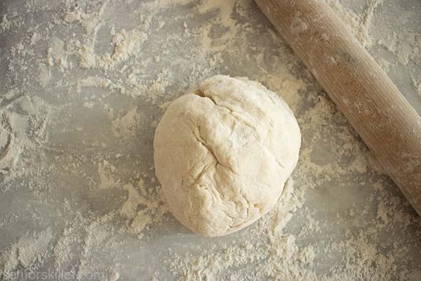 Pie dough ball on floured surface