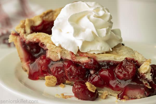 Baked cherry lattice pie slice with whipped topping