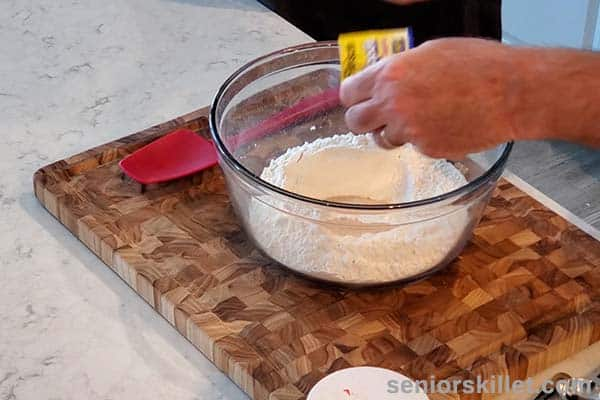 Homemade dough ingredients added to bowl