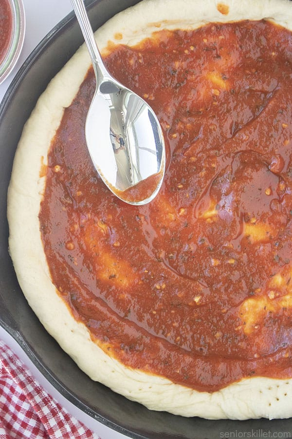 Homemade Sweet Pizza Sauce on a crust with spoon